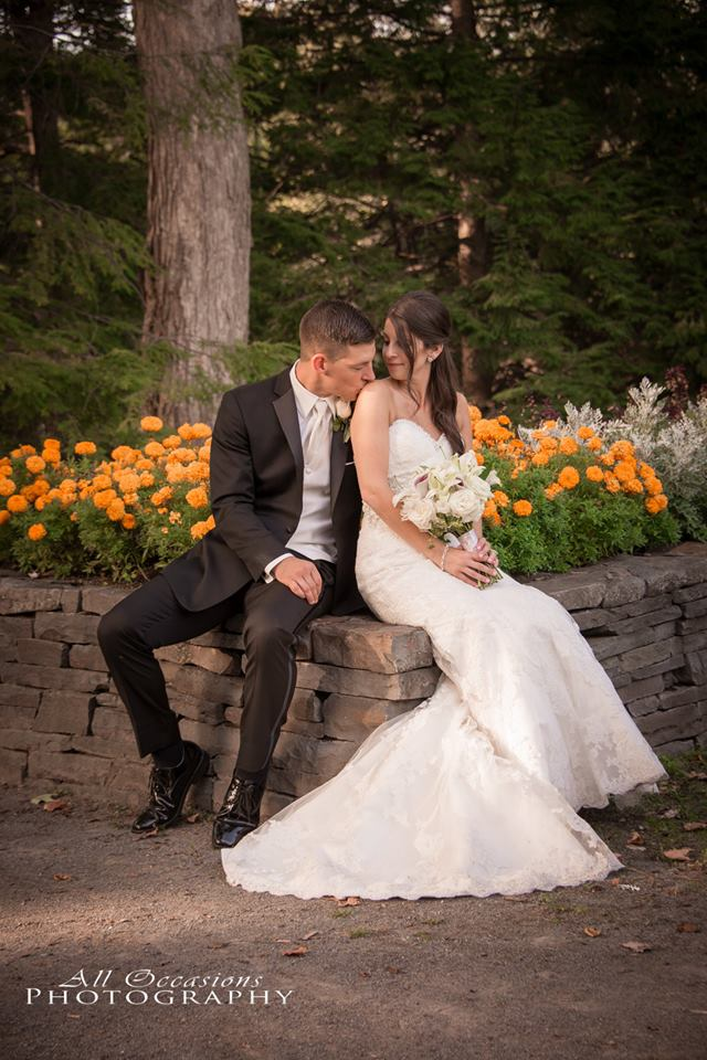 All Occasions Photography Albany NY - Wedding Photography Groom Kissing Brides Shoulder Amongst Flower Bed