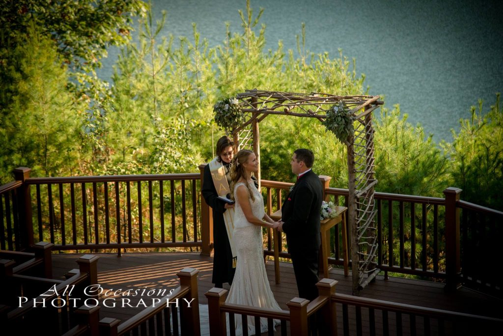 All Occasions Photography Albany NY - Wedding Photography Groom & Bride Standing Beneath Wooden Altar by Lake