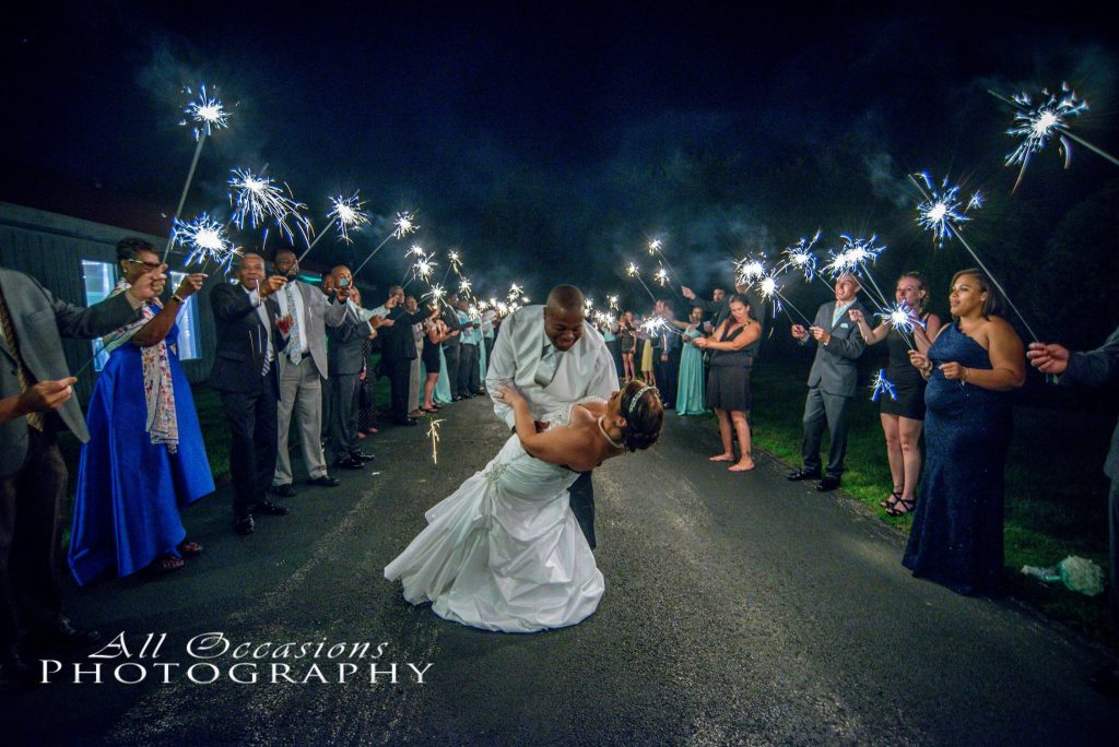 All Occasions Photography Albany NY - Wedding Photography Groom Dipping Bride While Party Holds Sparklers