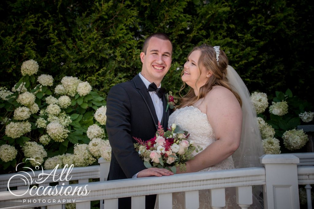 All Occasions Photography Albany NY - Wedding Photography Bride & Groom Standing by Fence Near Hydrangeas